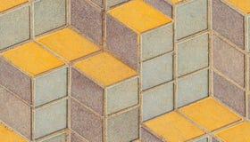 Superficie di vecchio pavimento intonacato con il rombo simmetrico di architettura geometrica gialla blu variopinta o il modello  immagine stock