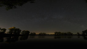 Superficie lisa del lago del bosque en un fondo del cielo nocturno a Imagenes de archivo
