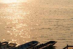 Superficie ondulada del agua con la luz del sol y la fila anaranjadas que brillan de los barcos de cola larga que parquean en la  imagen de archivo libre de regalías