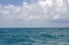 Superficie regolare del mare contro un fondo di un cielo nuvoloso fotografia stock