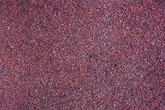Superficie roja granosa, fondo con las pequeñas piedras Fotografía de archivo libre de regalías
