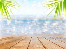 Superficie vuota di una tavola di legno su un fondo della spiaggia e delle foglie di palma fotografie stock libere da diritti
