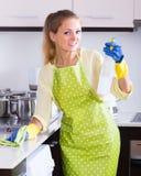 Superficies de la limpieza de la muchacha en la cocina Imágenes de archivo libres de regalías