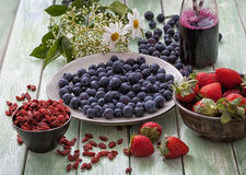Superfood: blueberries, blueberry juice goji seeds. And strawberries on a garden table Stock Image