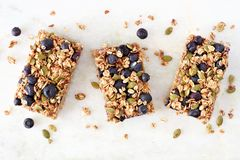 Superfood breakfast bars, above view on marble background. Superfood breakfast bars with oats and blueberries, above view on white marble background Stock Photo