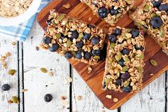 Superfood breakfast bars with oats and blueberries on wood board. Overhead scene on rustic background Stock Photo
