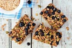 Superfood breakfast bars, overhead on white wood. Superfood breakfast bars with oats and blueberries, overhead on white wood background Stock Photography