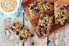 Superfood breakfast bars on wood board, above scene. Superfood breakfast bars with oats and blueberries on wood board, above scene on rustic background Stock Photo