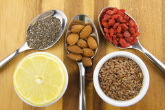 Superfood. Lemon, Linseeds, Chia seeds, nuts and goji berries on wooden background Stock Image