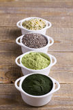 Superfood raw seeds and powder. Body building powders and health food on wooden background. Superfood served in small bowls Stock Photo