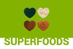 Superfoods文本和四心脏与spirulina粉末、可可粉、杏仁面粉和可可椰子糖在绿色ba 库存图片