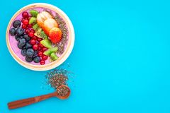 Superfoods. Acai smoothie bowl with fresh fruits, berries, chia seeds on blue background top view space for text stock image