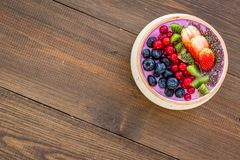Superfoods. Acai smoothie bowl with fresh fruits, berries, chia seeds on dark wooden background top view space for text royalty free stock image