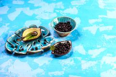 Superfoods antioxidant of indian mapuche. Bowl of fresh maqui berry on blue background, top view Authentic lifestyle image royalty free stock photos