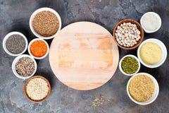 Superfoods en graangewassenselectie in kommen met houten raad voor uw tekst op grijze concrete achtergrond Royalty-vrije Stock Afbeelding