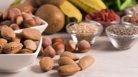 Healthy vegan food. Superfoods on a gray background with copy space. Nuts, beans, greens and seeds. Healthy vegan food stock footage