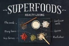 Superfoods On Black Chalkboard Background: Goji Berries, Chia, Mung Beans, Buckwheat, Quinoa, Sunflower Seeds. Top View