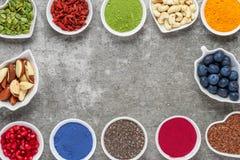 Superfoods på en grå bakgrund med kopieringsutrymme matcha, acai, gurkmeja, frukter, bär, muttrar och frö Strikt vegetarianmat arkivfoton