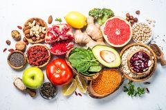 Superfoods on white background. Healthy vegan nutrition. Superfoods on white background. Organic food and healthy vegan food. Legumes,  nuts, seeds, greens, oil Royalty Free Stock Photography