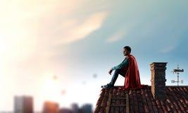 Superheld auf Dach Gemischte Medien stockfotografie