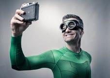 Superheld, der ein selfie mit einer Weinlesekamera nimmt Lizenzfreies Stockfoto