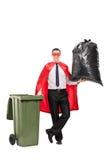 Superheld, der eine große Abfalltasche hält Stockfotos