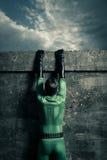 Superheld, der eine Wand klettert Lizenzfreies Stockfoto