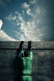 Superheld, der eine Wand klettert Lizenzfreie Stockfotos