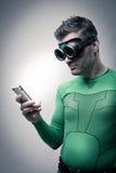 Superheld, der einen Smartphone verwendet Stockbilder
