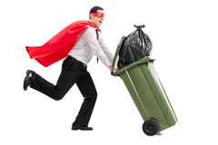 Superheld, der einen vollen Abfalleimer drückt Stockfotografie