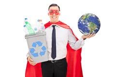 Superheld, der Papierkorb und die Erde hält Stockfotografie