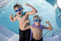 Superhelden zeigen ihre Muskeln durch Swimmingpool Stockfotografie