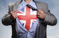 Superheldgeschäftsmann, der britische Flagge aufdeckt stockbild