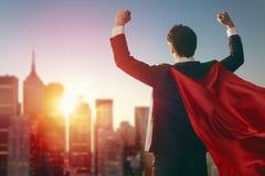 Superheldgeschäftsmann, der Stadt betrachtet stockbild