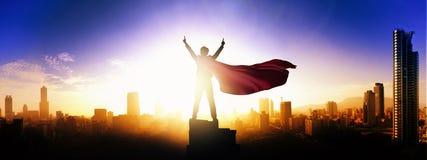 Superheldgeschäftsmann, der Stadtskyline bei Sonnenaufgang betrachtet lizenzfreie stockfotografie