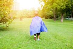 Superheldkind, das in Richtung zum Sonnenschein im grünen Park geht Lizenzfreies Stockfoto