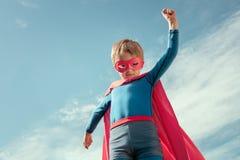 Superheldkind im roten Kap und in der Maske stockfotografie