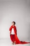Superheldmädchen im roten Kap, das im Studio aufwirft stockfotos