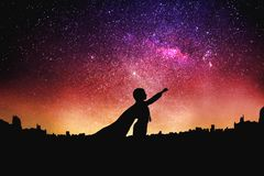 Superheldschattenbild am Nachtsternenklaren Himmelhintergrund stockfoto