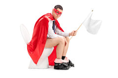 Superhero που κρατά μια άσπρη σημαία καθισμένη στην τουαλέτα Στοκ φωτογραφίες με δικαίωμα ελεύθερης χρήσης