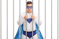 Superhero που στέκεται πίσω από τα κάγκελα σε μια φυλακή Στοκ Εικόνες
