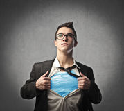 Superhero. Young businessman showing the superhero suit underneath his skirt stock photo