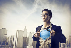 Superhero. Businessman showing the superhero suit under his shirt with cityscape in the background