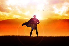 Superhero. Silhouette illustration of a superhero standing with mountain view as the background Royalty Free Stock Images