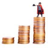 Superhero atop a pile of coins. Royalty Free Stock Photos