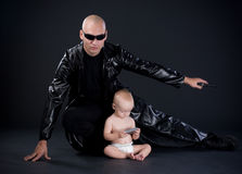 Superhero and baby. Superhero in black mackintosh and baby Royalty Free Stock Photo