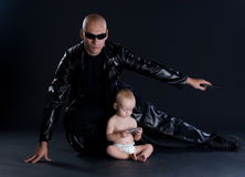 Superhero and baby. Superhero in black mackintosh and baby Royalty Free Stock Photography