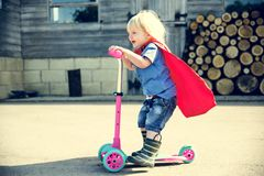 Superhero Baby Boy Using Scooter Adorable Concept Stock Photography