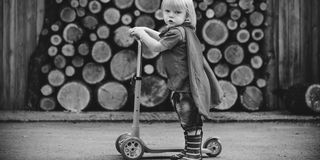 Superhero Baby Boy Using Scooter Adorable Concept Royalty Free Stock Image
