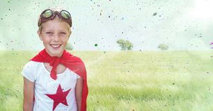 Superhero boy against meadow with flare and confetti. Digital composite of Superhero boy against meadow with flare and confetti Stock Images